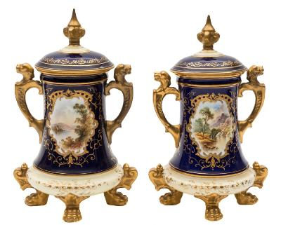 A pair of Coalport jars and covers of tapering form set on four lion paw feet, the handles with lion mask terminals, both decorated with gilt edged landscape panels, one by Percy Simpson, on gilt embellished royal blue grounds, green backstamps and pattern No V 6969/E, one captioned 'Mt. Venus', circa 1915-20, 17cm high, [knops and one handle restored].