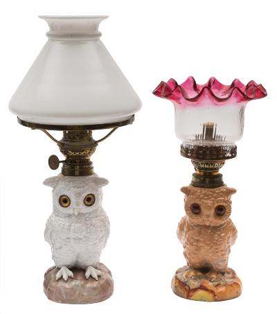 Two Continental table lamps in the form of owls each seated bird with glass eyes, one with milk glass shade, the other in cranberry and clear glass, early 20th century, 27 and 34 cm.