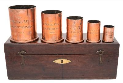 Sale FS40; Lot: 0667: A set of five George IV graduated copper wet measures of plain cylindrical form, each bears a crown and incised Amounderness, 1826, includes Imperial Quart, Pint, Half Pint, Gill and Half Gill, contained in a fitted wood case, the interior lid bears paper label for de Grave, Short & Fanner, Late M de Grave & Son, 59, St Martin Le Grand, London.