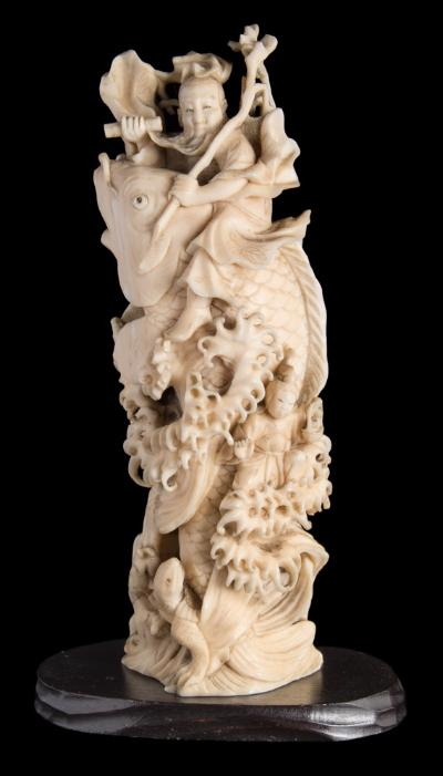 A Japanese carved ivory okimono, of Kinko Sennin, riding on the back of a carp unsigned, Meiji period, 15.5cm high.