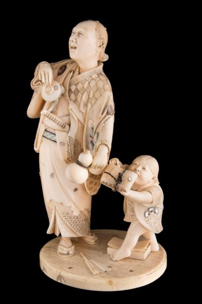 A fine Japanese carved and inlaid ivory okimono, signed Gyokusai inlaid with mother of pearl, wood and coral, the samurai holding a sake cup and gourd-shaped bottle, a small boy to one side trying to steal some dumplings from a packet attached to the samurai's robe, signed on a red lacquer tablet, Meiji, 19cm high [repair to one arm].