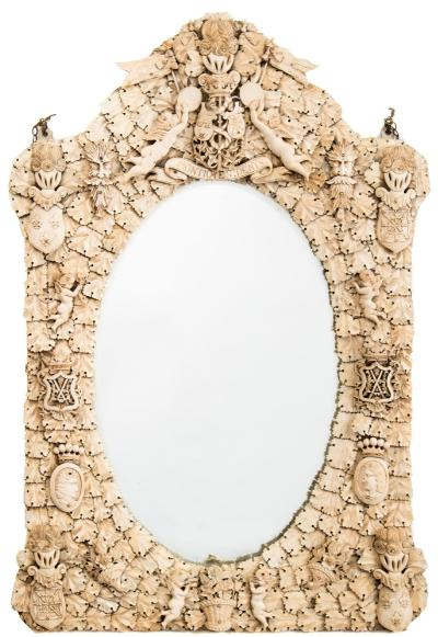 A large 19th century Dieppe carved ivory and bone wall mirror,: the oval bevelled mirror plate in an arched frame, the top with vase of flowers, coat of arms 'Montioye St Denys' flanked to each side by cherubs with tambourines, heraldic crests to each corner, cornucopia of flowers and leaves, 86cm x 57cm.