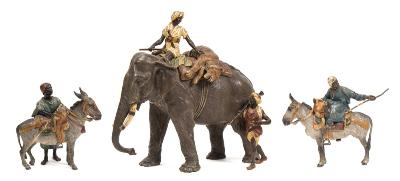 Franz Bergman, a 19th century Austrian cold painted bronze group of a tiger hunt the Arab astride an elephant with a dead tiger strapped behind, with walking attendant below, stamped to the underside with Bergman vase stamp, 'Geschutzt' stamp and numbered 3412, vase stamp and model No also stamped to the saddle blanket, 23.5cm high, together with two Arab boys with donkeys each bearing Bergman vase stamp, each 14cm high.