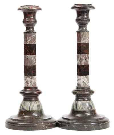 A pair of serpentine and marble candlesticks, with urn-shaped nozzles raised on segmented octagonal columns and circular domed bases, 39cm high.