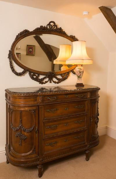An extensive French carved walnut ten piece bedroom suite, decorated with swags of foliage and tied ribbons, comprising - a pair of bow-fronted bedside cupboards with black variegated marble tops, each fitted with a drawer and enclosed by a door below, 43cm (1ft 5in) across, a kidney-shaped dressing table with oval swing frame mirror and single frieze drawer, 98cm (3ft 2 1/2in) wide, a bergere occasional chair with triple cane panel back and serpentine seat, an oval bevelled mirror with spiral ribbon surround and ribbon tied floral foliate cresting, 101cm (3ft 3 3/4in) x 13cm (4ft 5in), a pair of small oval mirrors, 28cm (11in) x 41cm (16in), a side cabinet of D-shaped breakfront outline with a black and grey variegated marble top fitted with four central drawers flanked by a pair of enclosed cupboards, 142cm (4ft 8in) wide, a king size bed with shaped and rounded foot board and high panelled headboard, 183cm (6ft) wide and an armoire of D-shaped outline, with central oval mirror door, 175cm (5ft 9in) wide, each piece raised on turned, fluted and carved tapered legs.