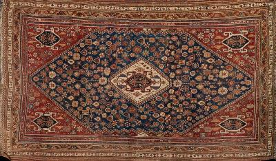 A Qashgai rug, the indigo field with a central ivory lozenge medallion and all over geometric designs, having brick red spandrels and main light brown serrated medallion meander border, 253 x 151cm.