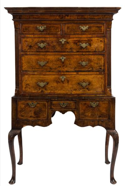 An early 18th Century walnut and inlaid chest on stand, bordered with sycamore lines, the upper part with a moulded cornice, fitted with two short and three long drawers between fluted canted angles, the stand fitted with three small drawers in the shaped apron, on shell carved cabriole legs, terminating in pad feet, 113cm (3ft 8 1/2in) wide, 173.5cm (5ft 8 1/4in) high.