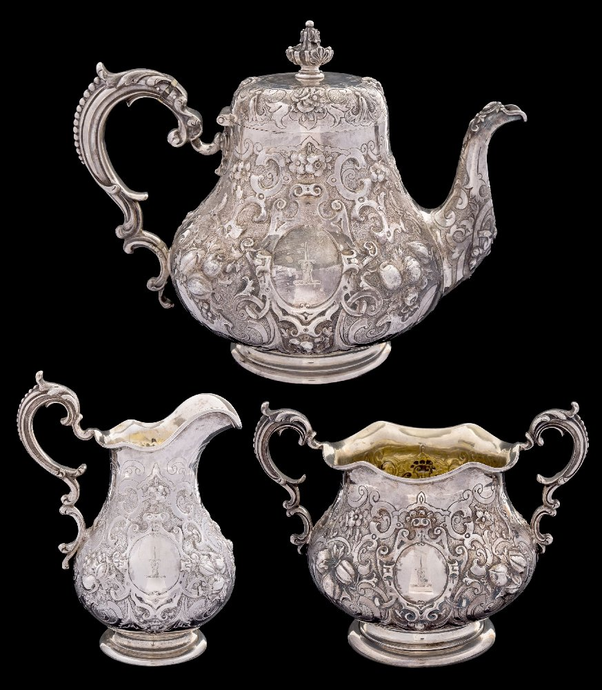 Sale FS41; Lot: 0110: A Victorian silver three-piece tea service, maker Robert Hennell III, London, 1861 crested, of squat globular form with embossed fruit, foliate and scroll decoration, raised on circular feet, total weight of silver 1465gms, 47.11ozs.