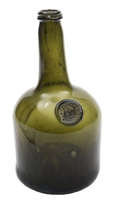 Sale FS41; Lot: 0486: An 18th century sealed glass wine bottle of squat cylinder form with shallow kick up, raised neck and string rim, the olive green body applied on the shoulder with a seal embossed 'B E 1773', 23 cm.