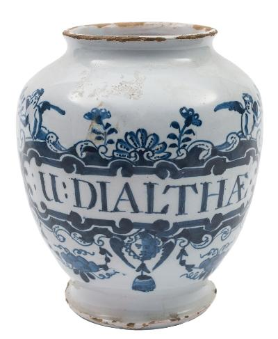 Sale FS41; Lot: 0566: A pair of London blue and white delftware dry drug jars each painted with an elaborate strapwork cartouche surmounted with a shell and two winged cherubs, a cupid's head and floral swags below, inscribed 'Bals:Lucat' and 'U:Dialthae', circa 1730-50, 16.5cm high [some damage and glaze losses]. *Note. Balsamum Lucatelli was used to treat ulcers and Unguentum Dialthae to decrease inflammation and heal wounds.