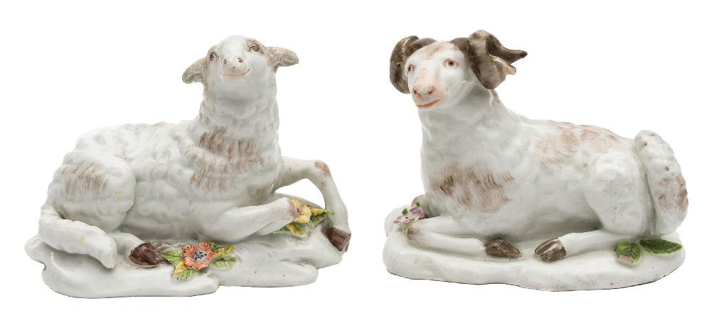Sale FS41; Lot: 0626: A pair of Chelsea models of a recumbent ewe and ram their fleeces with greyish brown markings, on mound bases applied with flowers and leaves, red anchor marks, circa 1755, 9cm [restoration to ewe's ears, minor losses to ram's horns and leaves].