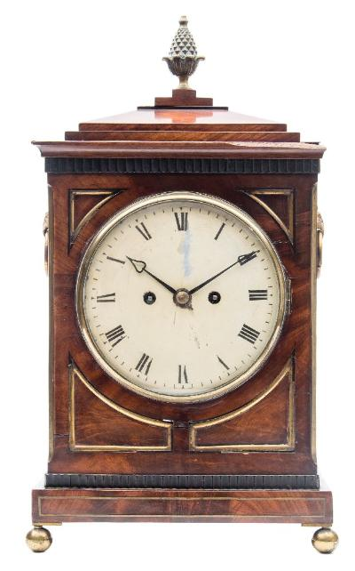 Sale FS41; Lot: 0895: A Regency mahogany bracket clock the eight-day duration, double-fusee movement of unusual shape having a verge escapement and a fully engraved backplate with the centre cartouche engraved RC, the seven-inch round painted convex dial having black Roman numerals and blued steel heart shaped hands, the mahogany case having a pediment top surmounted by a brass pineapple finial, with brass trim to the inset panels at each corner, with brass stringing to the lower base, brass fish-scale sound frets to the sides, cornucopia handles above the frets and standing on brass ball feet, height 50cms.