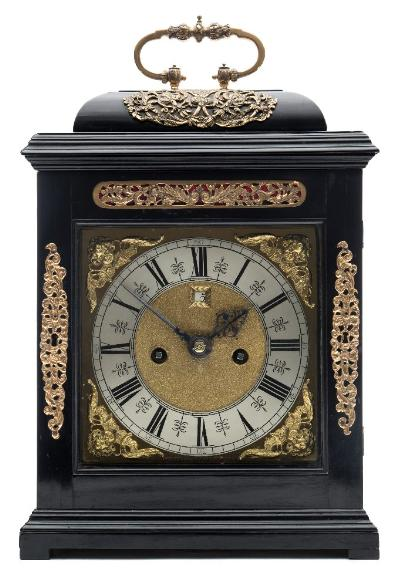 Sale FS41; Lot: 0896: John Knibb, Oxon, a late-17th century ebonised bracket clock of Phase IV design, the eight-day duration, double-fusee, five-pillar movement having a verge escapement and striking the hours on a bell with an outside countwheel, the backplate fully engraved with floral and wheat-ear border decoration, see RA Lee, the Knibb Family Clockmakers, plate 142, page 130, for a similar example, with the centre cartouche signed John Knibb, Oxon, the seven-inch square brass dial having a raised silvered chapter ring engraved with black Roman numerals, 'meeting-arrow-head' half-hour markings and outer five-minute Arabic numerals to the outer aspect, the matted dial centre having a date aperture with engraved surround, with the corners having cast-brass cherub-head spandrels and signed below the chapter ring at VI o'clock John Knibb, Oxon, with typical blued steel hands, the ebonised bell-top case with applied brass escutcheons to the front and top, with further inset brass fretwork above the dial, wooden fretwork to the case sides, the top surmounted by a brass carrying handle in a style typical of this maker, all standing on wood block feet, height 40cm handle up, 36.5cm handle down * Biography John Knibb was a member of the illustrious Knibb clockmaking family of London and Oxford, the most famous being Joseph Knibb, his older brother. John Knibb was born in 1650 and apprenticed to Joseph in circa 1664, who at this time had his workshop in Oxford. When Joseph moved to London circa 1670, John took on the running of the Oxford workshop receiving the Freedom of the City in 1672 having paid a fine. Obviously the clocks made by John resembled those of his illustrious brother Joseph and he obtained his cases from the same London source as Joseph. Some of John's movements may well have originated from the London workshop, identified by having both names signed on the clock, but John made movements in his own right and took on ten apprentices in his time including the excellent maker John Aldworth who, having moved to London circa 1697, continued to make clocks in the Knibb manner. John was a member of the City Council of Oxford from 1686 becoming a Bailiff in 1688 and twice Mayor, first in 1698 and again in 1710, as well as an Alderman and Keykeeper. John Knibb, of Smith Gate in the parish of Holywell, Oxon, died in July 1722 and was buried at St Cross church, Holywell therefore ending the Knibb family's influence as clockmakers. * Note. Reference Ronald A Lee, the Knibb Family - Clockmakers, the Manor House Press 1964; C FC. Beeson, Clockmaking in Oxfordshire, Museum of the History of Science, Oxford, 3rd Edition 1962.