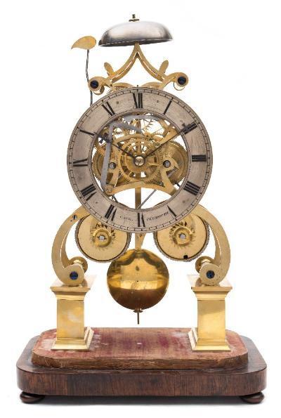 Sale FS41; Lot: 0899: James Edwards, Stourbridge, a striking skeleton clock the eight-day duration, double-fusee movement having scroll shaped plates standing on a pair of plinths, five-spoke wheelwork and striking the hours on a bell set to the top, the silvered chapter ring engraved with black Roman hour numerals and the retailer's name Cave, Plymouth, with blued steel Germanic cross hands, standing on a rosewood base with glass dome (damaged), height 38.5cm includes base and dome. * Biography James Edwards is recorded as working in Stourbridge, Worcestershire from before 1829, when he is known to have been in the High Street, until 1853 by which time he is known to be working at Hagley Road. by 1860 all records of him stop so presumably he had ceased trading or died at this point. Edwards was probably the first of the skeleton clock makers to produce top quality pieces on a fairly large scale, pre-dating both Evans of Handsworth and Smiths of Clerkenwell by at least ten years. * Note. Reference Derek Roberts, Skeleton Clocks Britain 1800-1914; Antique Collectors Club 1987; pages 173-177.