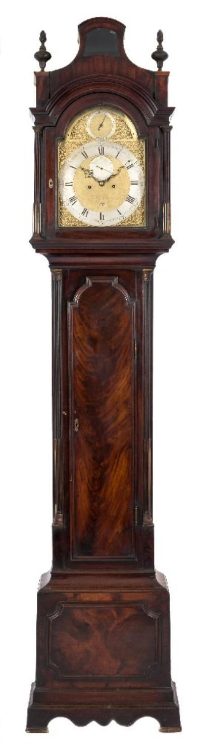 Sale FS41; Lot: 0905: A London style mahogany longcase clock having an eight-day duration movement with a half-dead beat escapement and striking the hours on a gong, the twelve-inch brass break-arch dial having a raised silvered chapter ring engraved with black Roman numerals and Arabic five-minute outer numerals, the matted centre having an inset silvered subsidiary seconds dial and date aperture, with the arch having a silvered 'strike/silent' dial, with oriental style cast-brass corner spandrels to the four corners and dial, the mahogany case having a shaped stepped moulding to the trunk door, fluted quarter columns to the trunk with brass stops and cast-brass capitals, with the hood having matching full pillars and surmounted by a pagoda top with carved wood flame finials, the base having a shaped raised panel, a double plinth and standing on bracket feet, height 246cms.