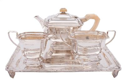 Sale FS41; Lot: 0007: A George V silver four-piece tea service, maker Elkington & Co, Birmingham, 1934/35 of rectangular outline with re-entrant corners, raised on shaped bases, includes, teapot, cream jug, sucriere and tray, total weight of silver 2368gms, 76.14ozs.