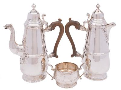 Sale FS41; Lot: 0008: A George V matched silver three-piece coffee service maker Mappin & Webb, London, 1931: the coffee pot and hot water jug of ovoid outline with domed hinged lids, reeded girdle on spreading circular feet, together with a near matching sugar basin, maker Mappin & Webb, Birmingham, 1933, total weight of silver 1538gms, 49.45ozs.