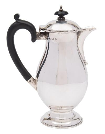 A George V silver hot water jug, maker RR, Birmingham, 1913 of plain baluster form, with shallow domed hinged lid with gadrooned border, raised on a circular spreading foot, 20cm high. 424gms, 13.64ozs.