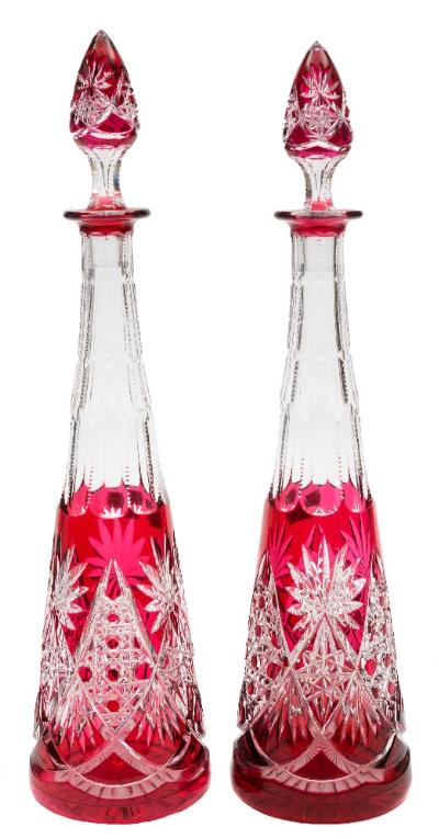 A pair of ruby overlaid clear glass decanters and stoppers of slender tapering form with star and hobnail cut decoration, 20th century, 41 cm.