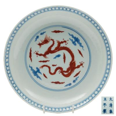Sale FS41; Lot: 0525: A Chinese underglaze blue and iron-red dragon dish the interior medallion decorated with a sinuous dragon amongst cloud and fire scrolls within double line and diaper borders, the reverse with four similar dragons between wave and line borders, apocryphal four-character Yongzheng mark within double circles, 20.5cm diameter [tiny re-stuck chip to rim].