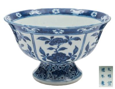 A pair of Chinese blue and white Ming-style stem bowls each painted in simulated 'heaping and piling' with panels of peony, peaches, pomegranate and lingzhi, apocryphal six-character Xuande marks, 19cm diameter.