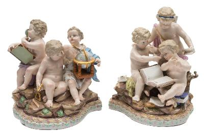 A pair of Meissen allegorical groups emblematic of Mathematics and Geography modelled after M V.Acier, each with three cupids on a rocky mound and ribbon tied moulded base, underglaze blue crossed swords marks and incised model nos.12 and 13, late 19th century, 20 and 18cm high [some losses] and ebonised wood stands.