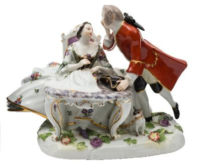 A Meissen group of lovers modelled after J J.Kandler the young woman wearing a floral crinoline dress and seated at a sewing table, her companion leaning towards her and wearing a gilt trimmed red coat, a pug dog amongst floral sprays at his feet, underglaze blue crossed swords mark and incised model no.551, 20th century, 18cm high.