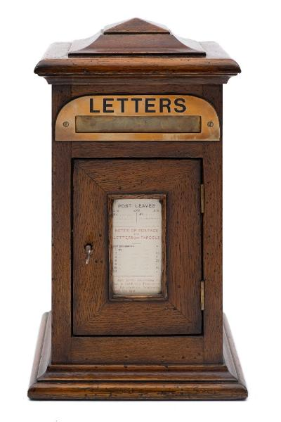 A late Victorian/Edwardian oak domestic letter box with stepped domed top, brass letter flap and hinged panel door inset with postal rates, on a moulded base, 33.5cm high.