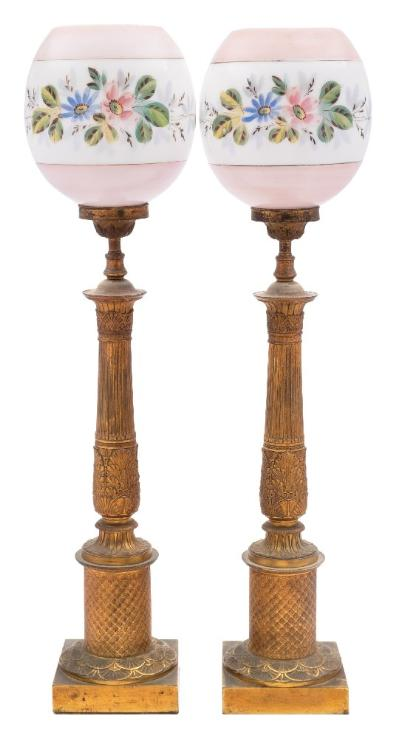 A pair of 19th century French gilt metal table lamps on reeded and acanthus decorated columns, with cylindrical lozenge decorated bases, on square plinths, with associated glass shades, fitted for electricity, 53cm high.