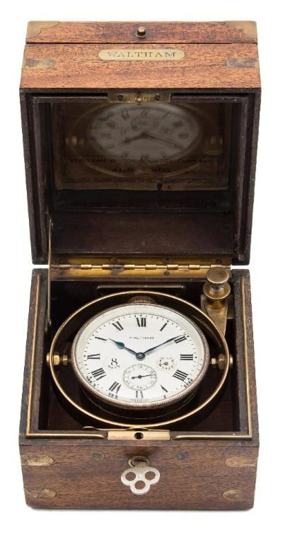 The Waltham Watch Co, a boxed 'chronometer' the eight-day duration movement having a lever escapement with a split-bimetallic balance, Brequet overcoil hairspring and keyless winding, with engine-turned decoration to the nickel-plated backplate stamped Waltham Watch Co 8 Days, 15 Jewels Adjusted, 22192011 and set within a brass gimbal, the round matt-silvered dial having black Roman numerals, a subsidiary seconds dial, a 'up-and-down' state of wind dial and signed Waltham, with blued steel spade hands, having a three-tier brass-bound mahogany box, the inside lid having pasted within a Waltham rating sheet from March 1924 stating Performance of Waltham 8 Day Lever Escapement Chronometer at Room Temperature and giving details of the performance over 26 days with a repeat of the clock number 22192011, dimensions 13cm x 13cm x 13cms.