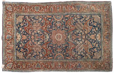 Sale FS41; Lot: 0936: A Kashan rug, the indigo field with a central geometric stellar medallion and all over palmette, flowerhead and foliate designs, enclosed by a main rust palmette meander border, 203cm x 130cm.
