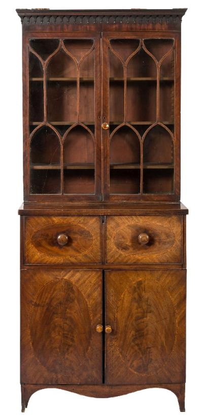 An early 19th Century mahogany and inlaid secretaire bookcase, crossbanded in kingwood bordered with boxwood lines, the upper part with a moulded swan neck broken pediment with circular and oval fan medallions, arcaded pendant hung frieze and adjustable shelves enclosed by a pair of pointed and ogee arched glazed panel doors, the lower part having a hinged fall enclosing a fitted interior with pigeon holes and satinwood veneered small drawers, the cupboard below fitted with a single long drawer and sliding trays enclosed by a pair of doors inlaid with oval lines, on splayed bracket feet, 90cm (2ft 11 1/2in) wide, 229cm (7ft 6in) high.