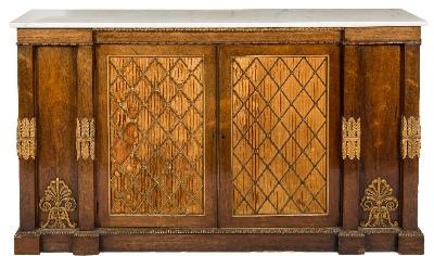 Sale FS41; Lot: 1025: A Regency rosewood, carved giltwood and brass mounted side cabinet, of breakfront outline, surmounted by a panel of white veined marble, having a brass C-scroll decorated moulded edge and reel turned frieze, the central cupboard enclosed by a pair of brass lattice and pleated silk panel doors, flanked by panels to either side with gilt anthemions at base, between foliate mounted plain pilasters, the side cupboards each enclosed by a moulded panel door, on a plinth base with reel turned moulding, 168.5cm (5ft 6 1/4in) long, 40cm (1ft 3 3/4in) deep, 96.5cm (3ft 2in) high.