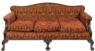 A carved mahogany settee in the Georgian taste, upholstered to match the pair of open armchairs, the serpentine panel back with beaded cresting, having padded arm supports and loose cushions to seat and back and with a gadrooned seat rail on acanthus decorated cabriole legs, terminating in claw and ball feet.