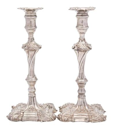 A matched pair of silver cast candlesticks, maker William Cafe, London, 1759 and 1765; with foliate decorated drip trays, urn-shaped sconces on a knopped and spiral twist stem, raised on a square stepped base with foliate corners, 25.5cm high, 1193gms, 38.37ozs.