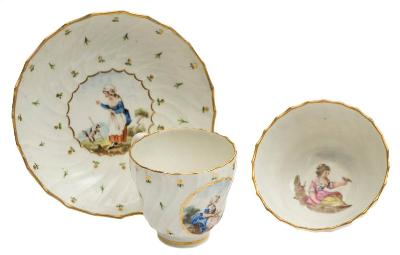 A Caughley teacup, coffee cup and saucer with painting attributed to Fidelle Duvivier of spirally fluted form, painted with children in rustic landscapes, one playing with a dog, another with a bird on her outstretched hand, on a ground of foliate and floral sprigs, decorated at the Chamberlain factory circa 1792, diameter of saucer 14cm *Note Saucer bears paper label for the 'Godden Reference Collection'. Literature: Geoffrey A Godden 'Chamberlain-Worcester Porcelain' pages 194/5/6 for illustrations and a discussion of this service.