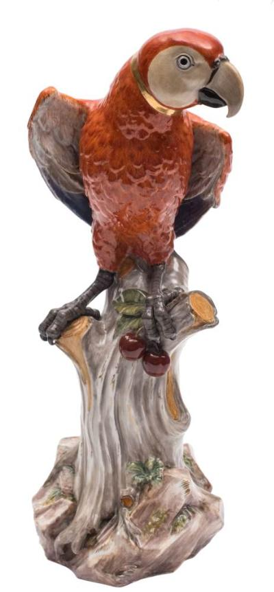 A large Meissen model of a parrot naturalistically modelled with gilt collar and red, grey, blue and yellow plumage, a bunch of cherries held in one claw, perched on a knarled tree stump and rockwork base, underglaze blue cancelled crossed swords mark, incised model no.A43, circa 1860/80, 42 cm.