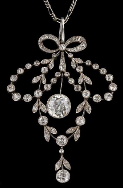 Sale FS45; Lot: 0230: A Belle Epoque diamond mounted, open work pendant the suspended principal diamond measures 8.2mm diameter x 4.7mm deep, estimated to weigh 1.90cts, within a surround of old brilliant-cut and rose-cut diamonds, suspending seven-stone drop and on fine-link chain, together with 'Tiffany & Co' box.