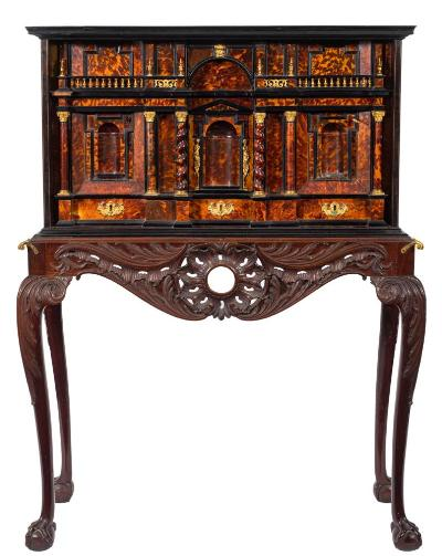 Sale FS45; Lot: 1080: An early 18th Century Italian tortoiseshell, ebony and coromandel wood architectural cabinet on a 19th Century carved mahogany stand, the gilt metal mounted cabinet fitted with an arrangement of drawers with baluster galleries and urn finials about a central portico drawer with applied Classical figures on Vitruvian scroll plinths, between spiral turned and plain columns with Corinthian capitals, the interior with various concealed drawers, the sides inlaid with brass geometric lines and satinwood husks, the stand with an acanthus scroll apron and central rocaille cartouche, on acanthus decorated cabriole legs, terminating in claw and ball feet, the cabinet 112.5cm (3ft 8 1/4in) wide, 61.5cm (2ft) high, 40cm (1ft 3 3/4in) deep - The stand 120cm (3ft 11in) wide.