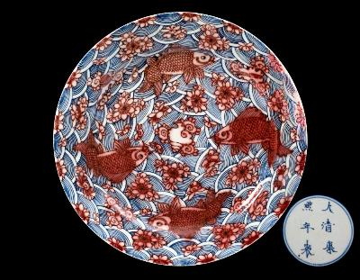 Sale FS45; Lot: 0588: A Chinese underglaze blue and copper-red charger boldly painted with four carp swimming amongst lotus blooms on a wave ground, the reverse with four Buddhist emblems, underglaze blue six-character Kangxi mark within double circles and of the period, 40cm diameter [restored section and crack to the rim]. * Bears a Sotheby's Belgravia label numbered 723949.