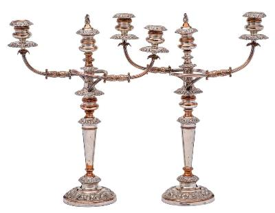 A pair of early 19th Century Sheffield Plate twin branch candelabra, maker J Watson and Sons with urn -shaped nozzles on reeded scrolling branches, raised on a tapering column and weighted circular base with embossed foliate and scroll decoration, 52.5cm high.