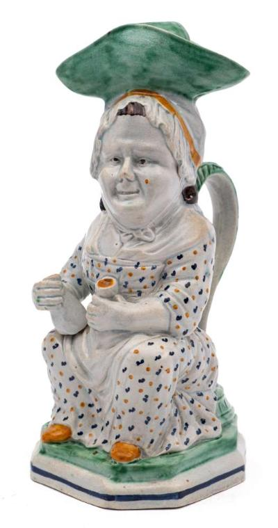 A late 18th century Prattware 'Martha Gunn' toby jug and cover modelled seated and wearing a large green hat over a mob cap, holding a jug of ale in her right hand, a glass in her left, on canted square base, circa 1790-1800, 28cm.