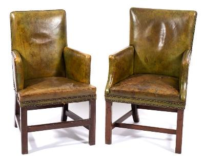 A pair of Georgian mahogany and leather club armchairs, of square form, with stuff over brass studded olive green leather upholstery on square chamfered legs, united by plain stretchers.