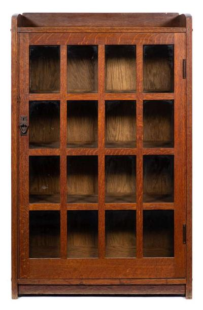 An oak Arts and Crafts bookcase, the three quarter galleried top over single bar glazed door enclosing shelves raised on end supports 89cm wide 142cm high (remains of label to back for Craftsman).