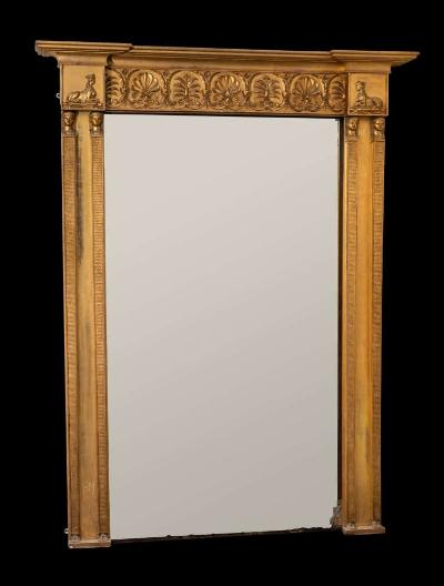 A fine Regency giltwood and gesso overmantel mirror, of large size in the Egyptianesque manner, having a reeded cornice of recessed breakfront outline, the frieze with applied anthemions and palm sprays within leaf cartouches, flanked by panels with sphinxes, the rectangular plate flanked by twin Egyptian monopediae stiles to either side and with scale ornament, 235cm (7ft 8 1/2in) x 180cm (5ft 11in).