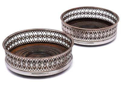 A pair of electro plated wine coasters of circular outline, with pierced trellis sides on a turned wood base, with beaded borders, 13cm diameter.
