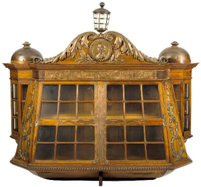 Sale MA14; Lot: 0179: A fine 'Foudroyant' oak and copper wall cabinet by Goodall Lamb & Heighway, Manchester, from ships timber and metal salvaged from HMS Foudroyant, styled in the form of the stern of the Foudroyant with copper and glass anchor light over arched transom, decorated with copper scroll mounts and circular portrait plaque of Nelson looking to sinister, flanked by domed finials, the copper mounted frieze inscribed '1798 Foudroyant 1801' over double glazed doors with copper strapwork and graduated laurel wreathes to sides and glazed quarter gallery style sections to either side, the base section with ropetwist border and inswept base in the manner of stern strakes, central rudder style foot and copper plaque ' Goodall Lamb & Heighway manufactured from the oak and copper salvaged from Nelson's 'Foudroyant', 163cm wide, 40cm depth, also together with a copy of an original brochure 'The ship of the century Nelson's flagship Foudroyant' in which the cabinet is illustrated as item number 36.