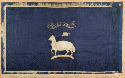 Sale MA17; Lot: 0113: A rare and well preserved Arctic exploration sledge flag for Admiral George Richards KCB, Commander of HMS Assistance in Sir Edward Belcher's expedition of 1852/3/4in search of HMS Erebus and HMS Terror of Sir John Franklin's Lost Expedition of 1845:, the flag with Admiral Richard's personal heraldry comprising a lamb and flag crest with motto 'Laus Deo' (Praise God) in white silk on a blue reserve, 46cm x77cm, mounted on a glazed frame with inscription.