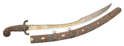 Sale SC22; Lot: 0201: A 17th century Turkish Kilij, the broad reinforced blade with single curved edge and double edged point, inset with gold koftgari and tughra, two further rectangular calligraphic panels surrounding a star, the downward swept hilt and handle inset with coral and turquoise, in a matching scabbard also inset five oval turquoise and gilt inscriptions, the reverse with floral geometric decoration, blade length 71cm.