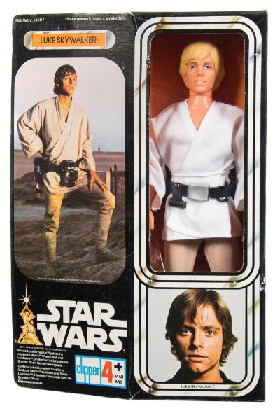 A 1977 issue Star Wars 'Luke Skywalker' 12 inch action figure by Clipper Toys, Amsterdam, in white tunic with utility belt, fawn trousers and white plastic boots, together with grappling hook and light sabre in original card case with celluloid window, the figure retained on the inner card with packing wire, blue Clipper logo to card, the case 33cm high.